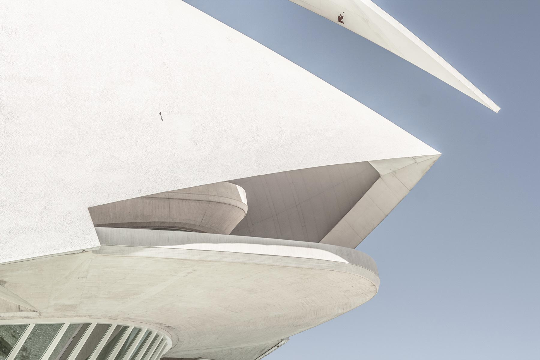 Close-up of the corner of a white, geometric building with both sharp points and round corners.